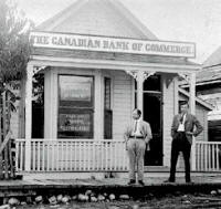 Two men standing in front of the Canadian Bank of Commerce.